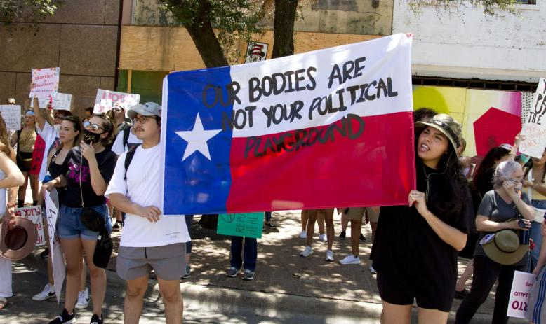 """A man and a woman hold a Texas flag with the text """"Our Bodies Are Not Your Political Playground"""" written on it"""