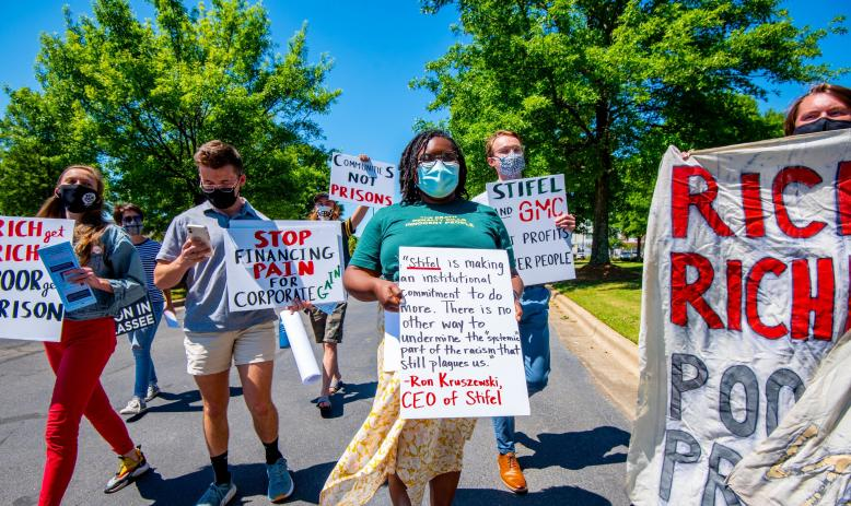 Several people walking down a street holding signs in protest of Alabama's prison lease plan