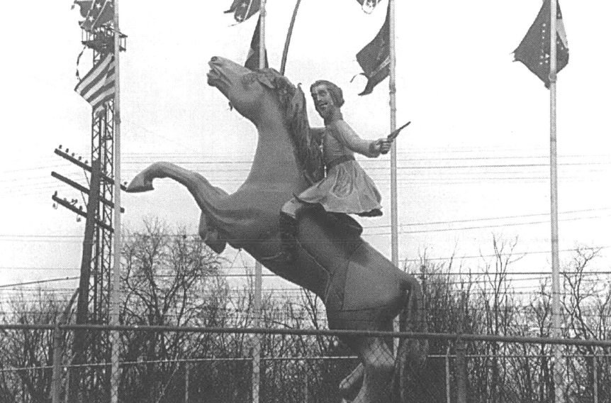 A black and white photo of a statue of a man on a horse, surrounded by several tattered flags, including Confederate flags.