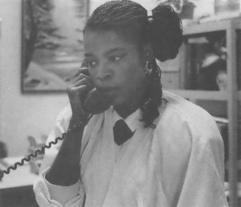 Black and white photo of a Black woman on the phone in an office.