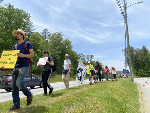 A line of marchers holding signs alongside a highway.